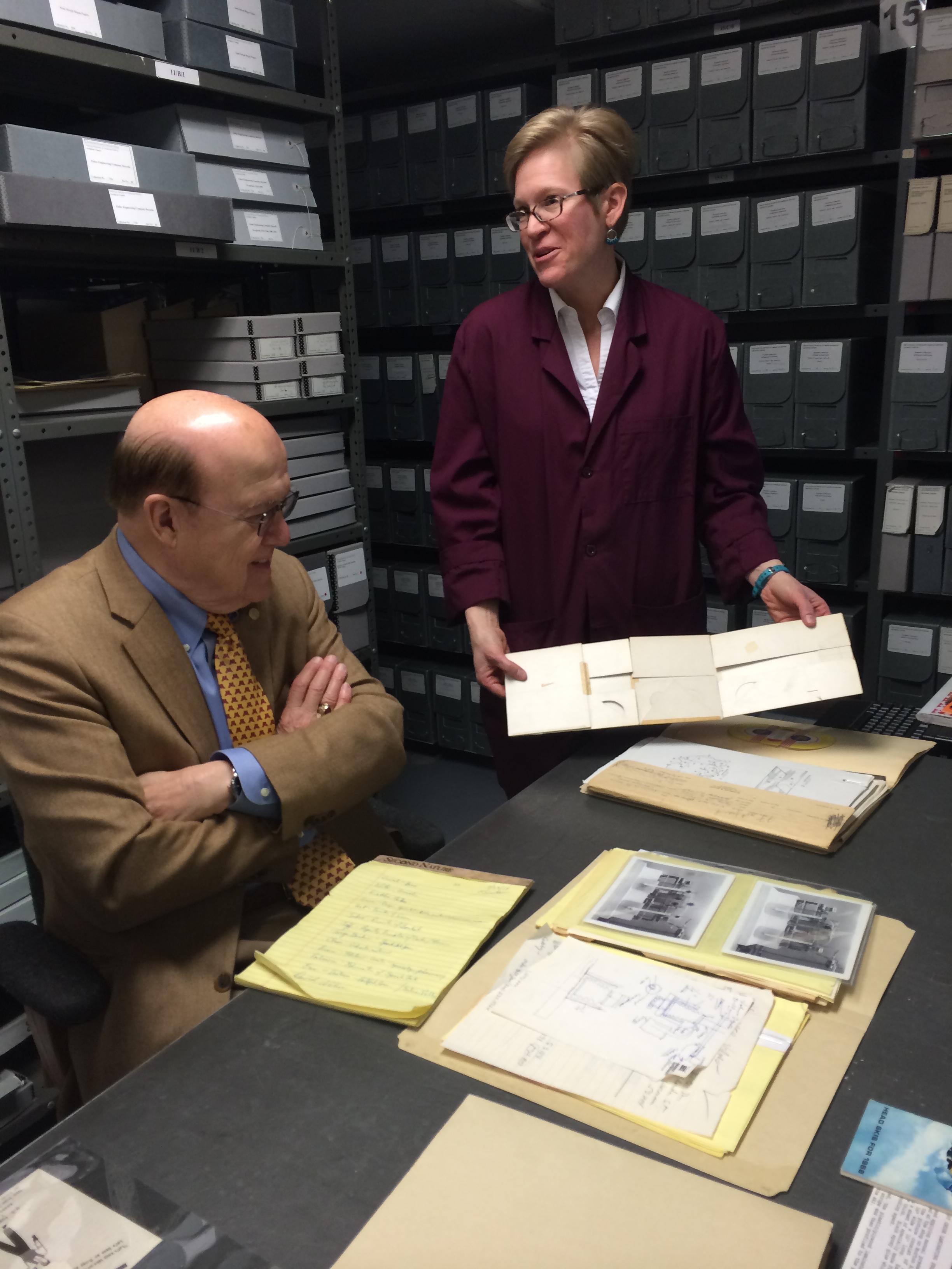 Archivist Alison Oswald shows Manny Villafaña archival documents.