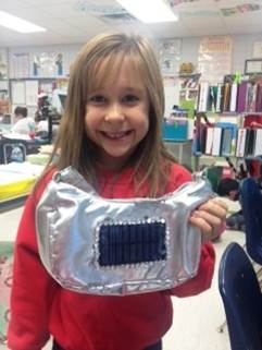 A young girl holds up her invention: The Solbrite.