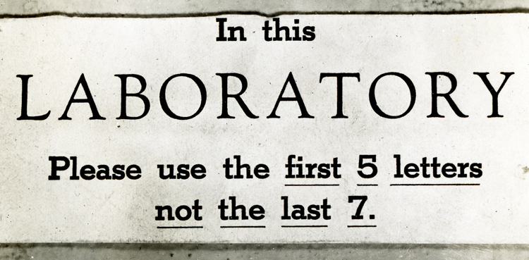 "IBM Science Laboratory sign reading, ""In this laboratory, please use the first 5 letters, not the last seven,"" meaning more labor and less oratory."