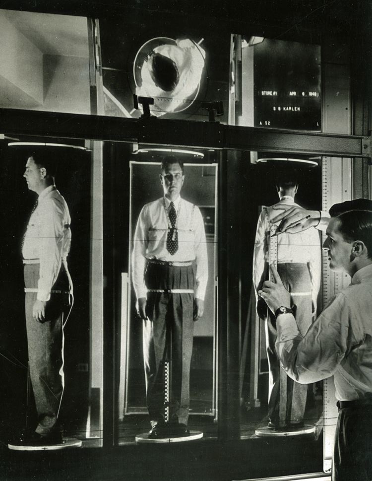 A projection of 3 views of a male customer's reflection in mirrors, from the side, front, and back. He is wearing a tape measure harness that goes around his neck, arm (at the shoulder), chest, waist, and hips. A shop clerk  at the left foreground holds a ruler up to a translucent screen to measure the space between the individual tapes.