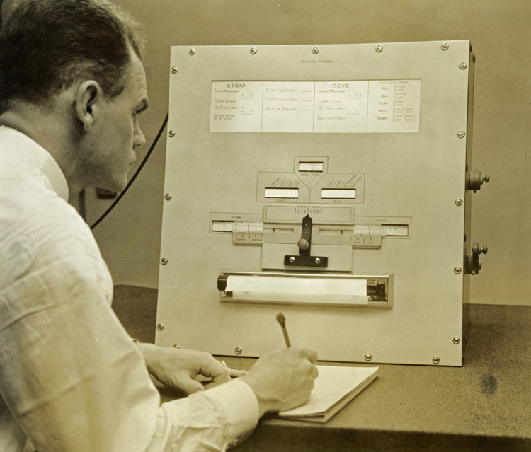 Side profile of man sitting at a desk, holding a pencil and writing on a pad of paper, looking at the PhotoMetriC calculator, which provides the measurements for the customer's clothing. The calculator appears to be about 2 feet square, with windows cut into a metal face plate. The windows show different measurements and takes into account the customer's posture and other factors.