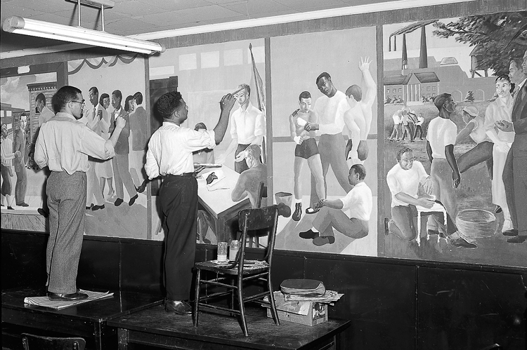 Two Black men standing on tables painting murals of Black men and boys at various activities.