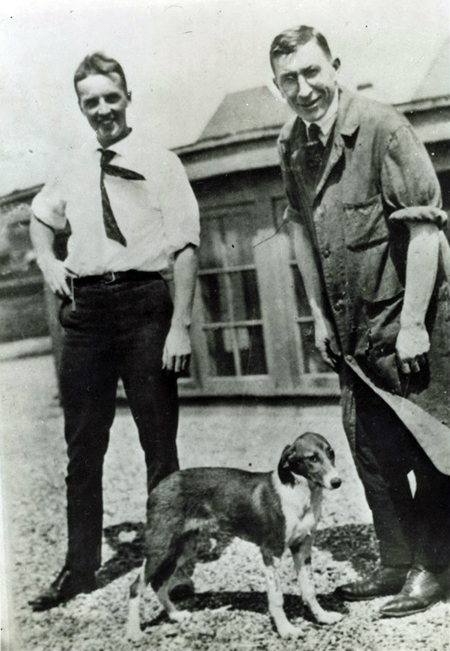 Outdoors photo of Charles Best (on left, in shirtsleeves), a dog in the center, and Frederick Banting on right, wearing a workshop duster.