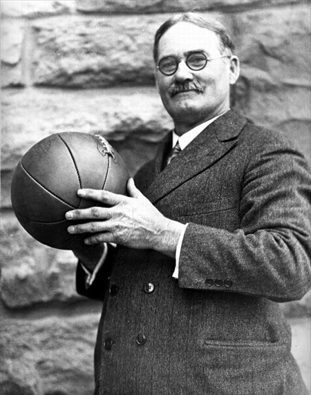 Three-quarter profile photo of James Naismith, wearing a suit and tie and holding a basketball.