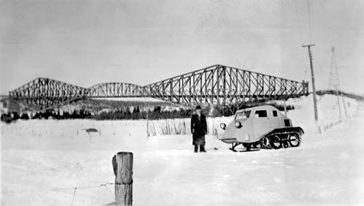Joseph-Armand Bombardier standing outside, on snow-covered ground, wearing a topcoat and hat, and standing next to his 1937 B7 snowmobile. A truss bridge is visible in the background.