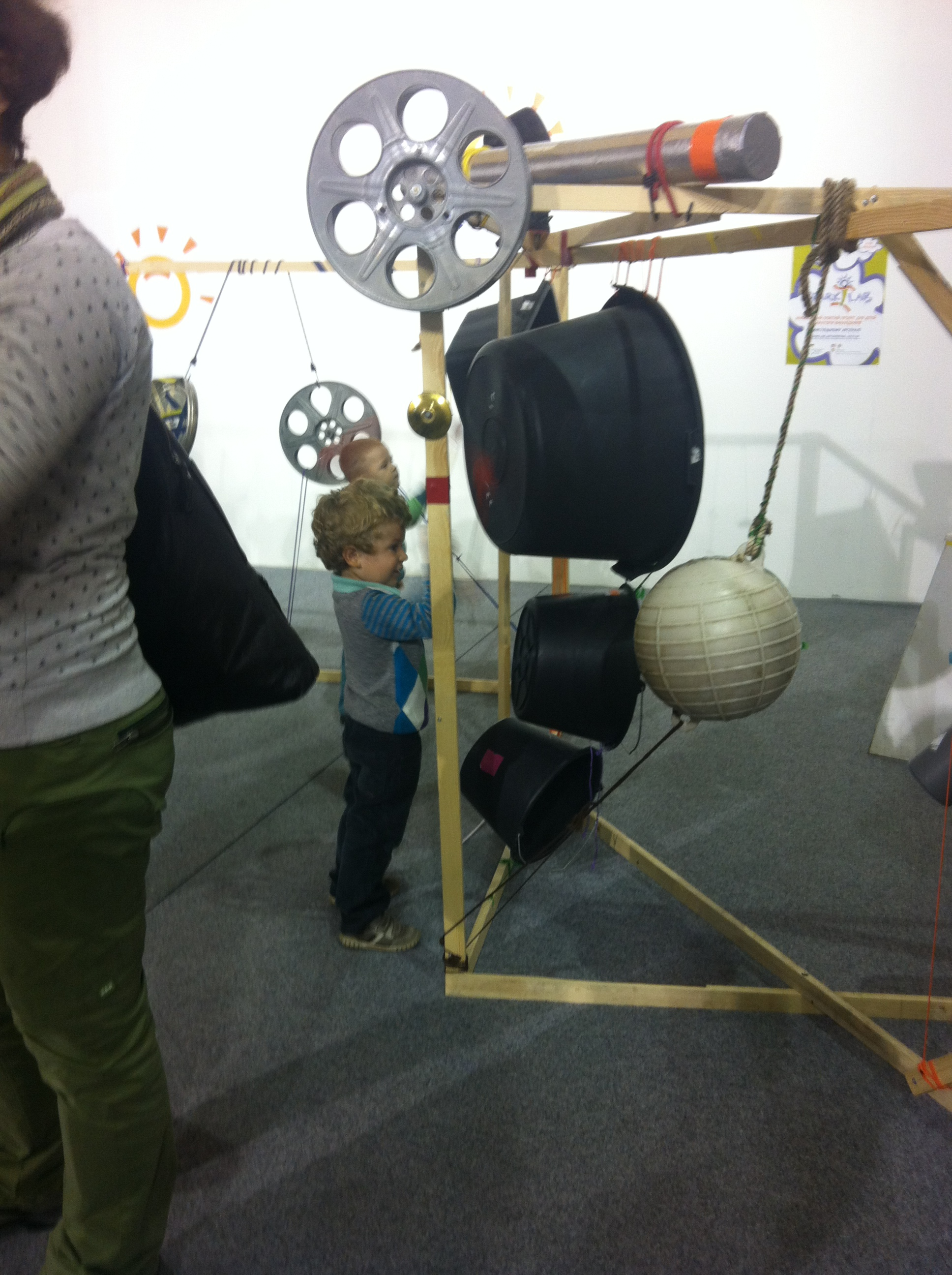 """Boy banging on a buoy that is part of a """"found object"""" percussion sculpture"""