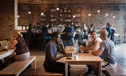Young professionals gather in an urban, modern coffee shop.