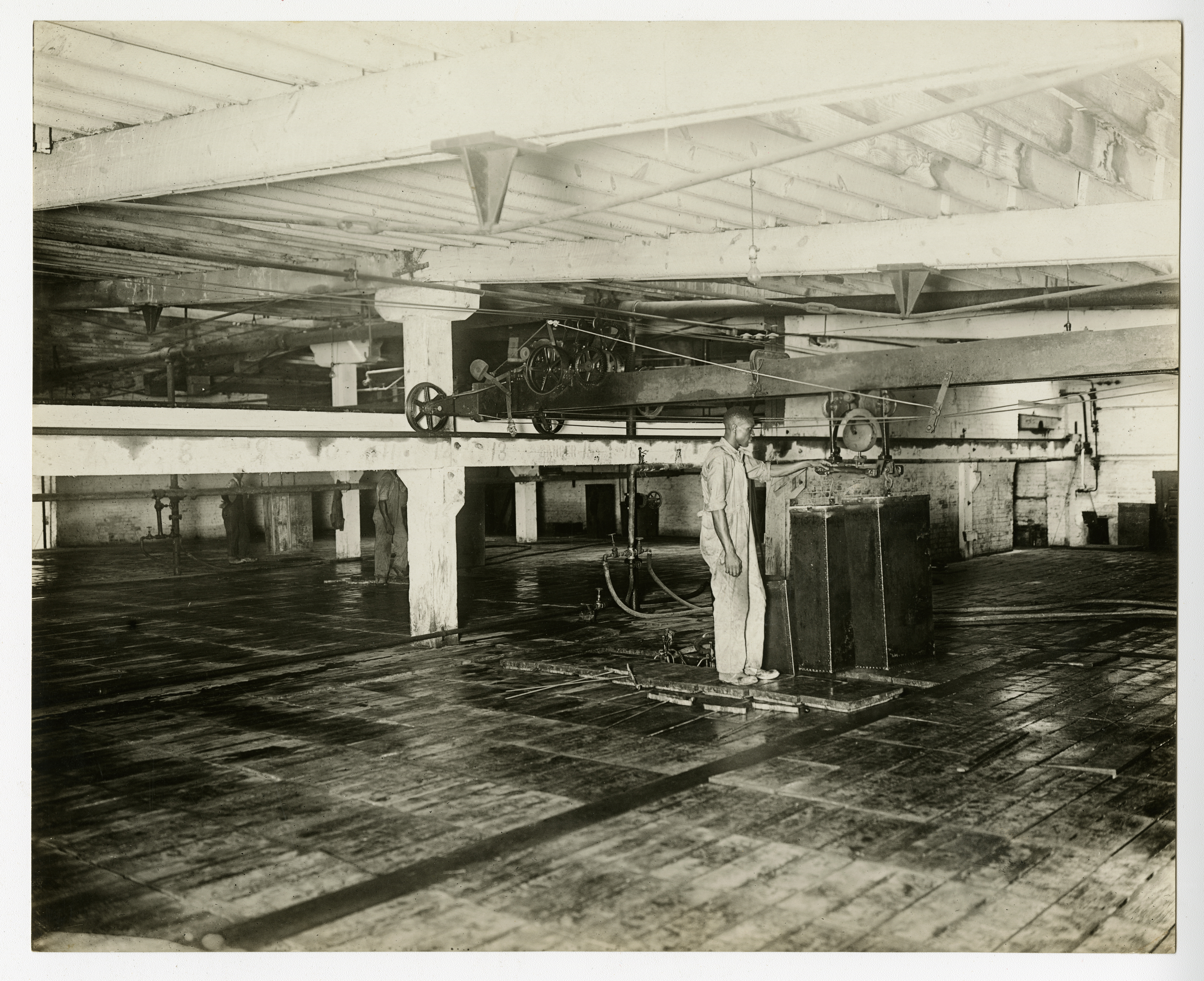 A worker operates the can hoist on the floor of a Frick-built ice plant, undated (AC0293-0000012).