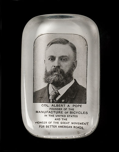 "A glass paperweight featuring Albert A. Pope (1843-1909), Hartford bicycle manufacturer and leader of the American ""good roads"" movement, about 1890s"