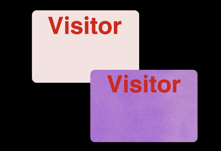"""Two badges reading """"Visitor,"""" one with white background and the other with a purple background"""