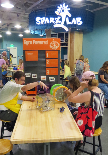 Side view of an activity table in SparkLab. Facilitator Zach Etsch sits in profile on the left side of the table. He is animated and gesturing to the young girl and woman who are working on an activity with gyros on the other side of the table.