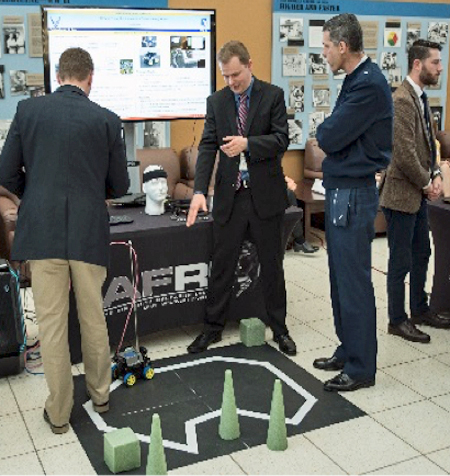 In a trade show setting, a small robot navigates an obstacle course on the floor while one man explains its movement to another man. Other men look at other displays.
