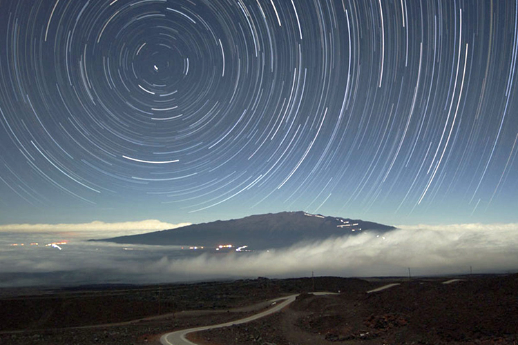 A landscape scene, showing a curving road that winds from the foreground to the background, passing under low-lying clouds, and heading toward a mountain. City lights are at the right of the image and the sky is filled with circular star trails.