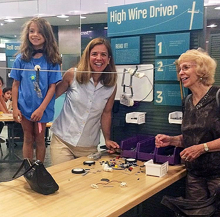 One older adult woman, one adult woman and one female child are gathered around an activity table and smiling. The picture is taken from the side view. In the middle of the picture is a light wooden table. On the table are lego pieces and wire is strung a