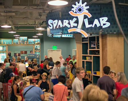 A view of the Sparklab interior space from the front of the room looking towards the back of the room. On the left and center of the picture, in the foreground is a curved table with many people standing around and some sitting on stools. In the distance