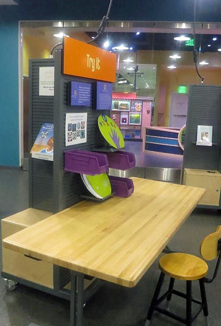 Side view of an activity station comprising a stool and a light wooden table with an attached gray panel holding 3 purple plastic buckets, 2 green circles on gray shelves, 2 purple text panels, and a large orange text panel that reads Try It.