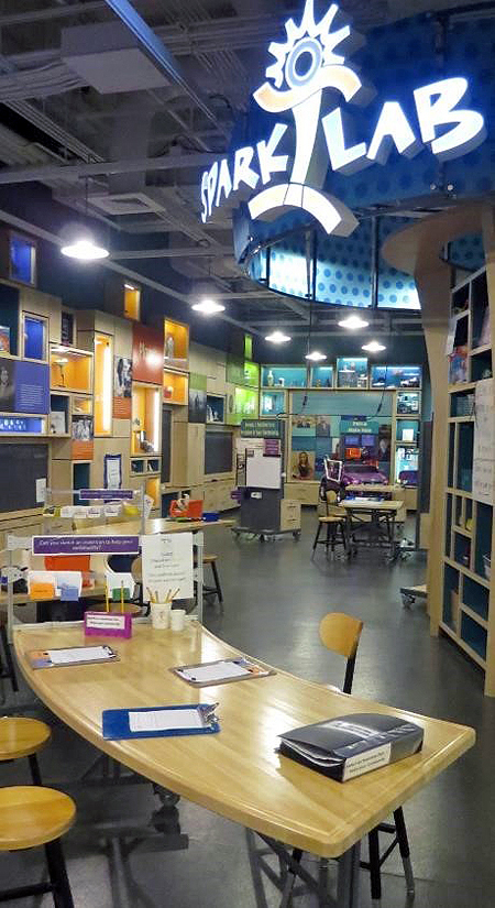 View of the Sparklab interior space from the front of the room. In the left foreground is a curved table with clipboards. In the distance is a wall with colorful display boxes, a wooden shelf unit, and the lighted sparklab sign overhead.