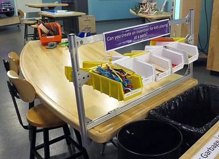 A curved, light wood table and two stools. Two vertical posts and a connecting horizontal plastic bar attached to the table hold white and yellow plastic bins filled with craft supplies in them.