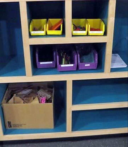 Close-up of shelves with blue interiors. On the shelves are yellow and purple plastic bins with craft supplies in them. On the bottom shelf is a cardboard box with pieces of cardboard in the box.