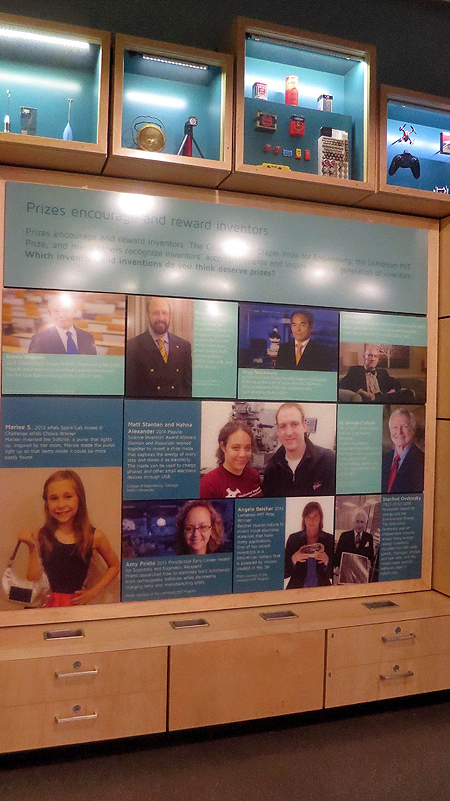 A wall in sparklab has blue text panels arranged across it. Each of the blue panels features a picture of an inventor with text about their invention.