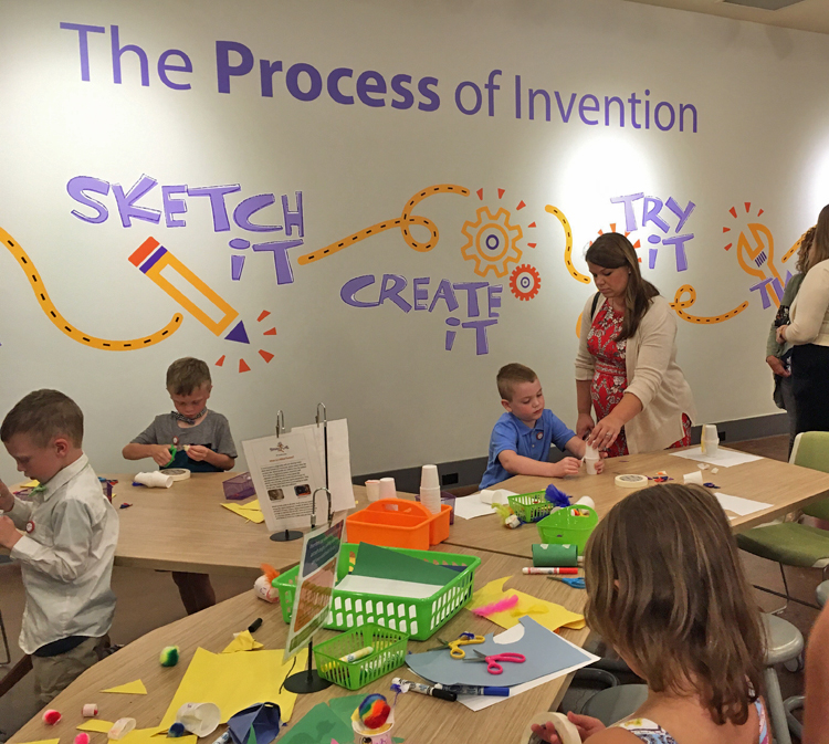 """3 young boys and 1 young girl work at activity tables, using craft materials in front of them. An adult woman assists 1 boy. """"The Process of Invention"""" is written in large letters on the wall, along with the illustrated words Sketch It! Create It! Try It!"""
