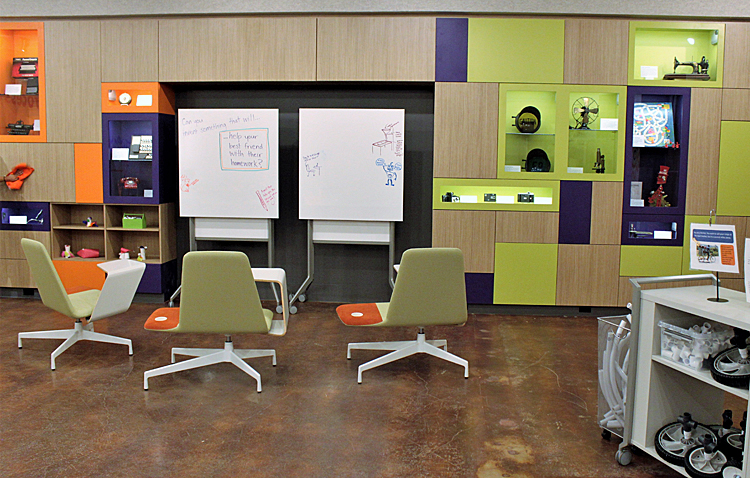 The empty SparkLab. On the right, a cart holds wheels and PVC pipe for building vehicles. In the center, 2 large sketch pads face 3 chairs with attached desks. On the wall, cubbies display inventions—microscope, sewing machine, electric fan, and more.