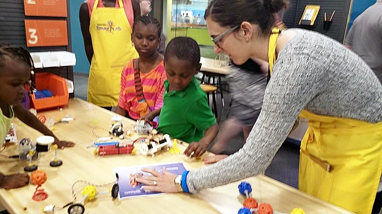 A SparkLab facilitator helps a young boy and girl with an activity. The children are seated at a table covered with activity components and the facilitator is leaning over the table to assist them.