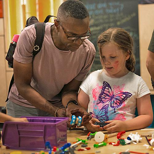 An adult man is working with a young girl on an activity in SparkLab
