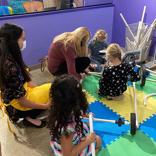 3 young girls, an adult woman, and a woman facilitator work on building a vehicle with PVC pipe