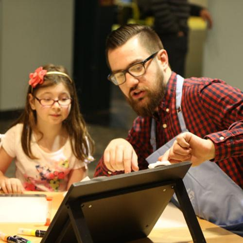 A facilitator works with a young girl on a Spark!Lab invention activity (Michigan Science Center)