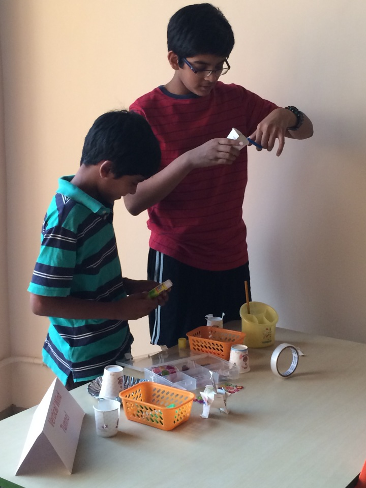 Two boys create flying inventions out of craft materials.