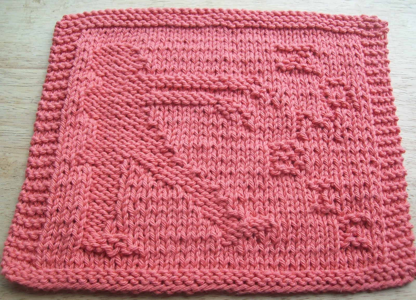 A pink knitted dishcloth incorporating a zombie into the design.